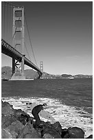 Surfer scrambling on rocks below the Golden Gate Bridge. San Francisco, California, USA (black and white)