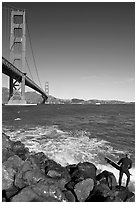 Surfer poised to jump in water below the Golden Gate Bridge. San Francisco, California, USA (black and white)
