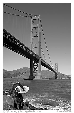 Surfer stepping on rocks and Golden Gate Bridge. San Francisco, California, USA (black and white)