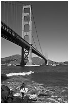 Surfer and wave below the Golden Gate Bridge. San Francisco, California, USA (black and white)
