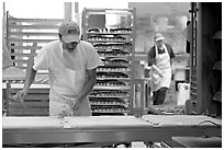 Baker hand-coating lofs of bread. San Francisco, California, USA (black and white)