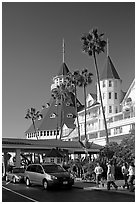 Entrance of hotel del Coronado, with cars and visitors wolking. San Diego, California, USA (black and white)