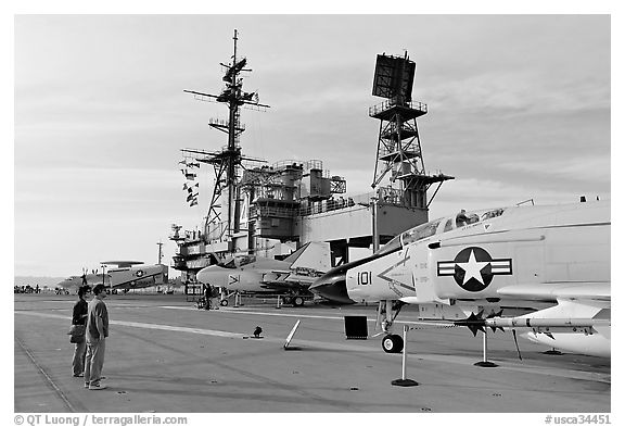 Couple looking at fighter aircraft on the Flight deck of USS Midway. San Diego, California, USA (black and white)