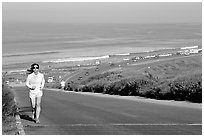 Woman jogging on raod,  Torrey Pines State Preserve. La Jolla, San Diego, California, USA (black and white)