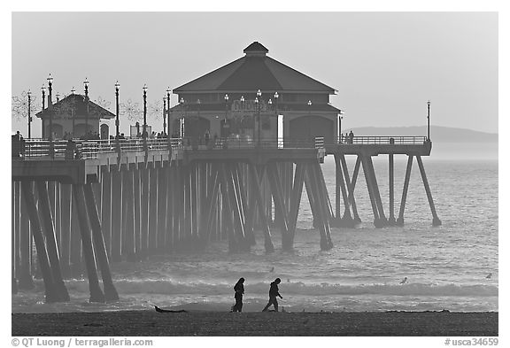 Beachgoers and Huntington Pier, late afternoon. Huntington Beach, Orange County, California, USA (black and white)