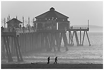 Beachgoers and Huntington Pier, late afternoon. Huntington Beach, Orange County, California, USA ( black and white)