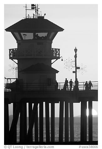 People and pier silhouetted by the setting sun. Huntington Beach, Orange County, California, USA (black and white)