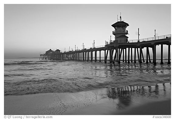 Huntington Pier reflected in wet sand at sunset. Huntington Beach, Orange County, California, USA (black and white)