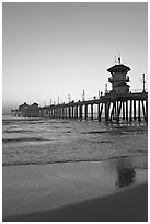 Huntington Pier and reflections in wet sand at sunset. Huntington Beach, Orange County, California, USA ( black and white)