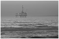 Off-shore petrol extraction  platforms, sunset. Huntington Beach, Orange County, California, USA (black and white)
