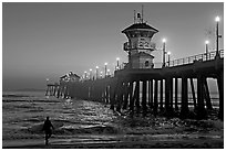 Surfer and Huntington Pier lights at twilight. Huntington Beach, Orange County, California, USA ( black and white)