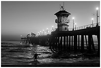 Surfer entering water next to the Huntington Pier, sunset. Huntington Beach, Orange County, California, USA ( black and white)