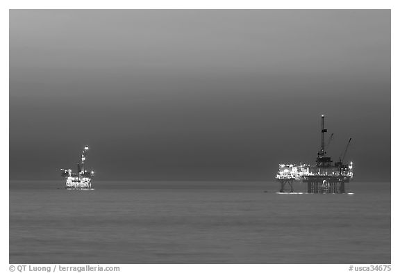 Oil drilling platforms lighted at dusk. Huntington Beach, Orange County, California, USA (black and white)