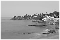 Rocky coastline with waterfront houses at dawn. Laguna Beach, Orange County, California, USA (black and white)