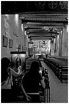 Two women light up candles in the Serra Chapel. San Juan Capistrano, Orange County, California, USA ( black and white)