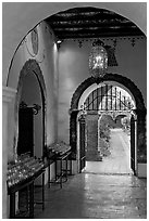Corridor with candles next to the Serra Chapel. San Juan Capistrano, Orange County, California, USA ( black and white)