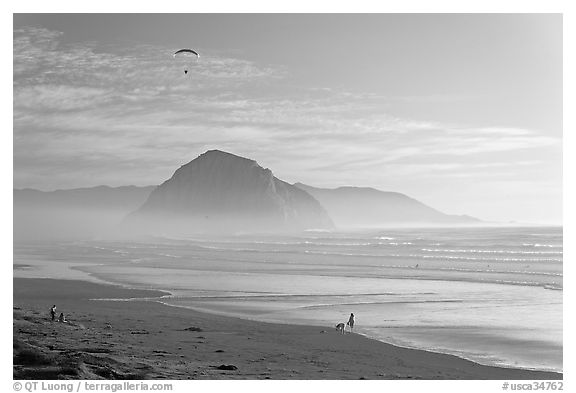 Motorized paraglider, women walking dog, with Morro Rock in the distance. Morro Bay, USA (black and white)