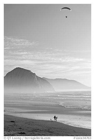 Motorized paraglider, women walking dog, and Morro Rock seen from Cayucos Beach. Morro Bay, USA (black and white)