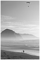 Motorized paraglider, women walking dog, and Morro Rock seen from Cayucos Beach. Morro Bay, USA ( black and white)