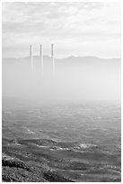 Chimneys of power plant emerging from the fog. Morro Bay, USA (black and white)