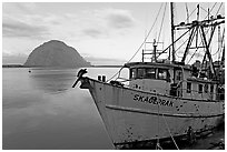 Baat with rusted hull and Morro Rock. Morro Bay, USA (black and white)