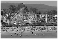 Beachgoers, and Santa Cruz boardwalk roller-coaster. Santa Cruz, California, USA ( black and white)