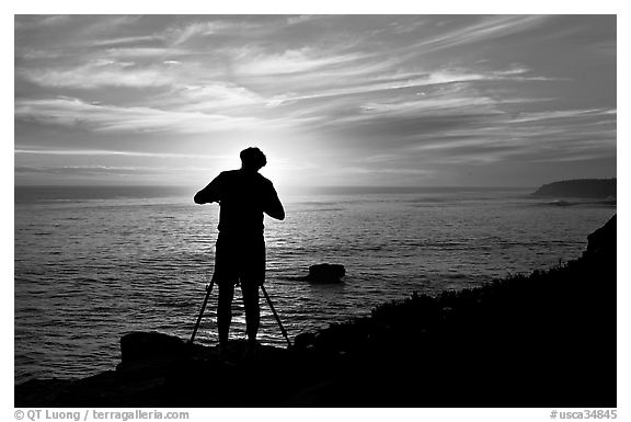 Photographer on cliffs at sunset. Santa Cruz, California, USA (black and white)