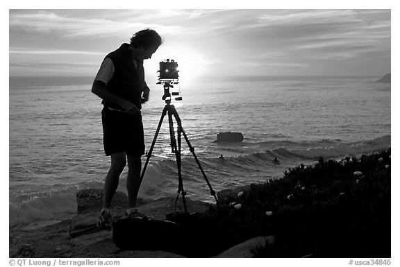 Photographer and large format camera on tripod at sunset. Santa Cruz, California, USA (black and white)