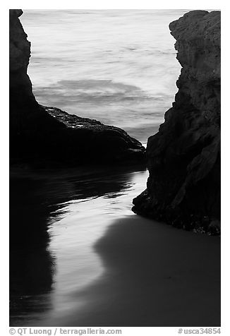 Reflection on wet sand through rock opening, Natural Bridges State Park, dusk. Santa Cruz, California, USA (black and white)