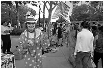 Woman in clown costume waiving American Flag, Independence Day. San Jose, California, USA (black and white)