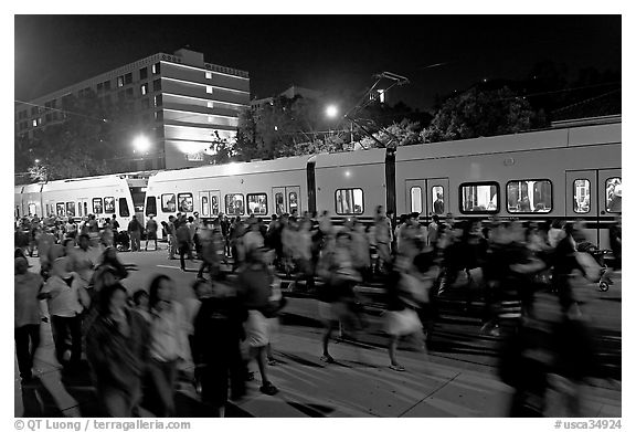 Crowds and light rail on San Carlos Avenue at night, Independence Day. San Jose, California, USA (black and white)