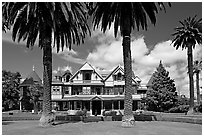Palm trees and mansion facade. Winchester Mystery House, San Jose, California, USA (black and white)