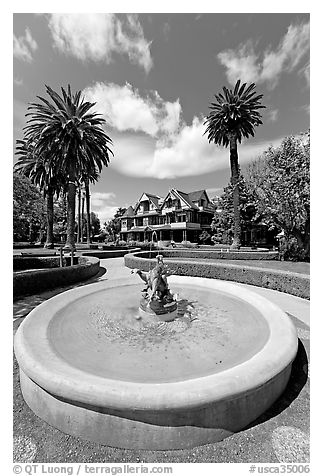 Wide view of fountain and mansion. Winchester Mystery House, San Jose, California, USA (black and white)