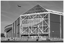 HP Pavilion with person and plane, late afternoon. San Jose, California, USA ( black and white)