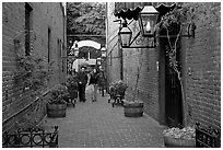 Couple walking in an alley of brick walls, San Pedro Square. San Jose, California, USA ( black and white)