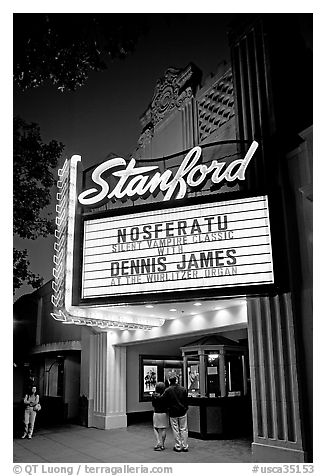 Couple standing in front of Stanford Theatre at night. Palo Alto,  California, USA (black and white)