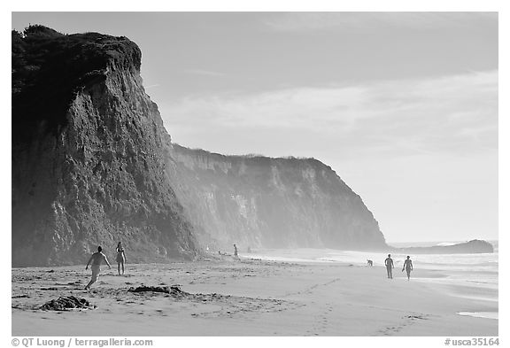 People strolling and playing below cliffs, Scott Creek Beach. California, USA (black and white)