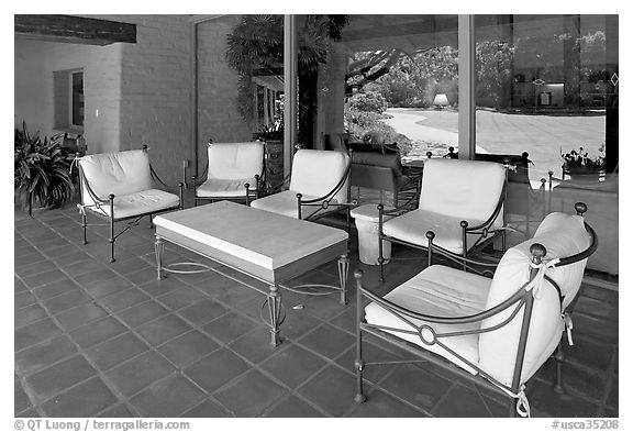 Chairs and coffee table on porch, Sunset gardens reflected. Menlo Park,  California, USA (black and white)