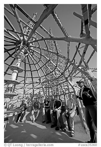 Tour guide and group in the Gazebo of the Watts Towers. Watts, Los Angeles, California, USA (black and white)