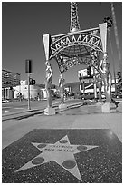 Star from the Hollywood walk of fame and gazebo with statues of actresses. Hollywood, Los Angeles, California, USA (black and white)