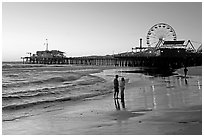 Couple on beach, with pier in the background, sunset. Santa Monica, Los Angeles, California, USA ( black and white)
