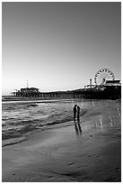 Couple standing on the beach at sunset, with pier and Ferris Wheel behind. Santa Monica, Los Angeles, California, USA (black and white)