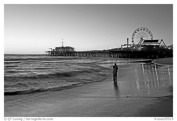 Couple reflected in wet sand at sunset, with pier and Ferris Wheel behind. Santa Monica, Los Angeles, California, USA (black and white)
