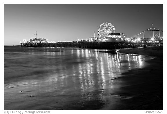 Pier and Ferris Wheel reflected on beach at dusk. Santa Monica, Los Angeles, California, USA (black and white)
