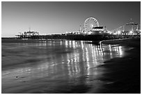 Pier and Ferris Wheel reflected on beach at dusk. Santa Monica, Los Angeles, California, USA ( black and white)