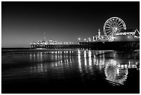 Ferris Wheel and pier reflected on wet sand at night. Santa Monica, Los Angeles, California, USA (black and white)