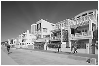 People jogging and strolling on beach promenade. Santa Monica, Los Angeles, California, USA (black and white)