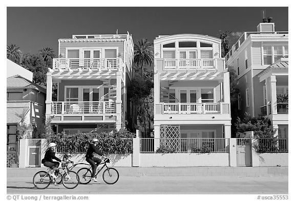 Family cycling in front of colorful beach houses. Santa Monica, Los Angeles, California, USA