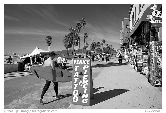 Black and white picture photo surfer walking on ocean front walk venice los angeles california usa
