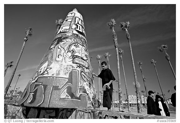 Man painting inscriptions on a graffiti-decorated tower. Venice, Los Angeles, California, USA (black and white)